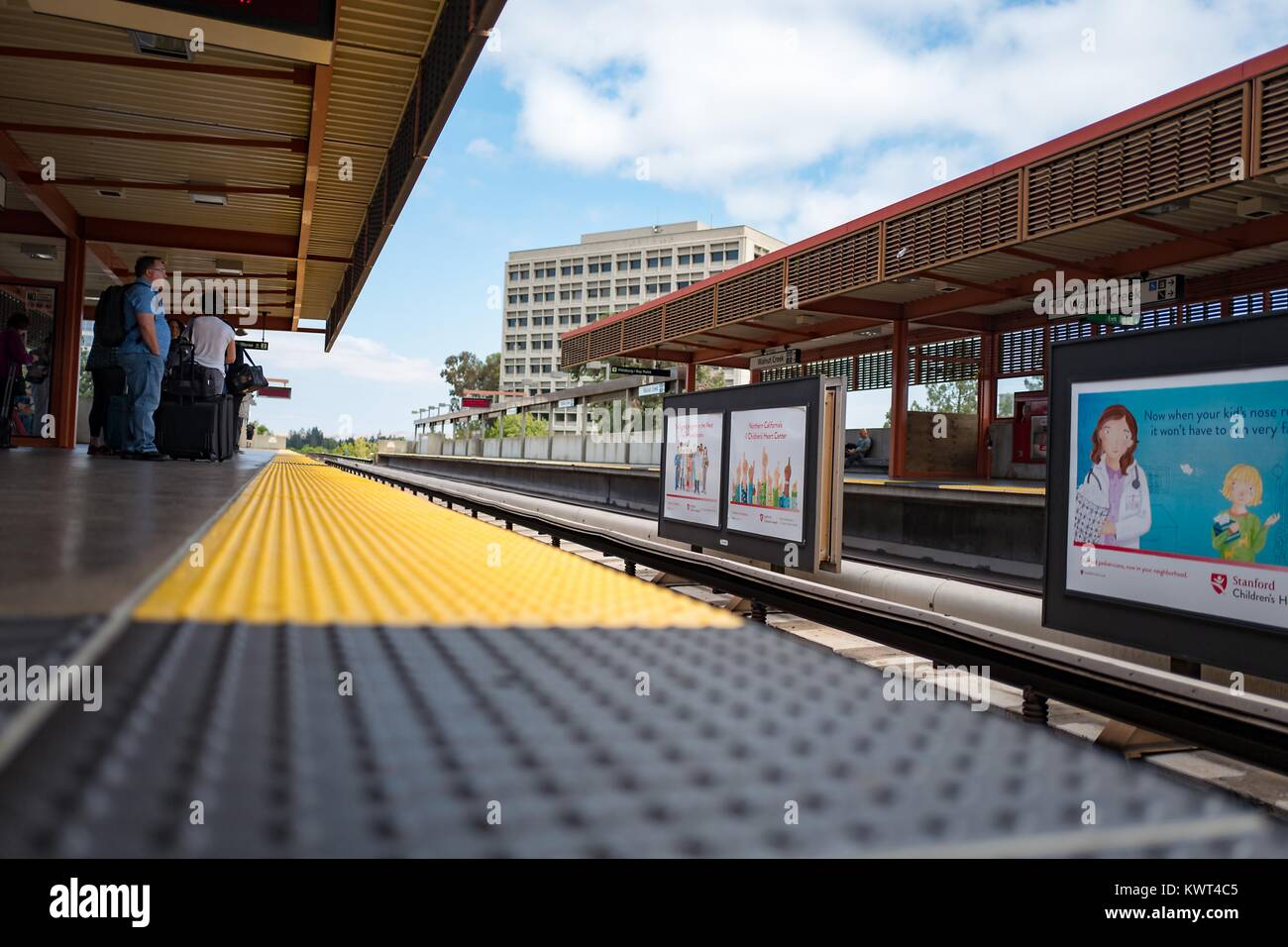 Low-angle view of passengers waiting for a train, seen from the edge of the platform, at the Walnut Creek, California - Stock Image