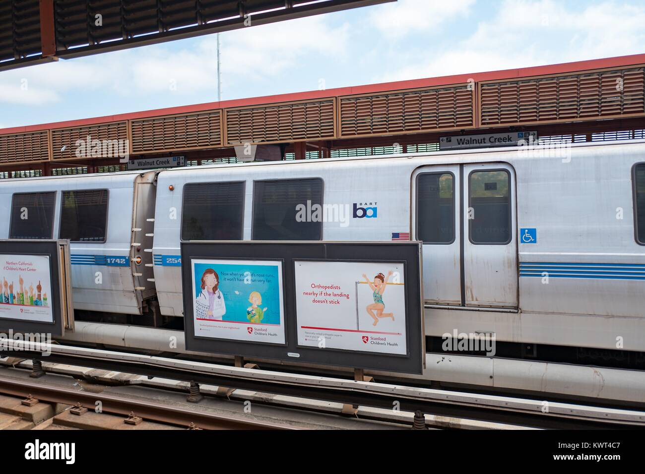 A BART train approaches the platform and prepares to load passengers at the Walnut Creek, California station of - Stock Image