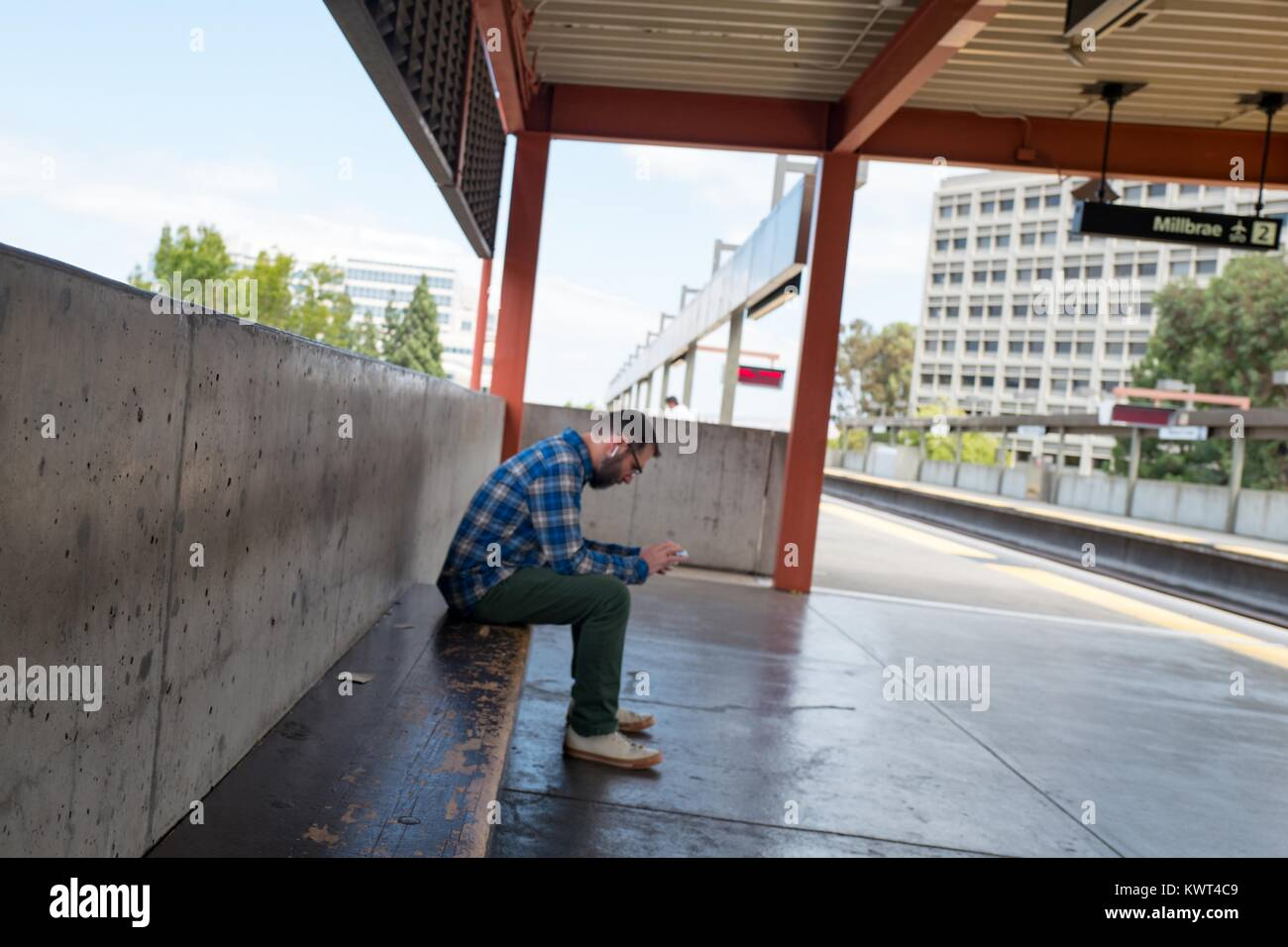 A man wearing a flannel shirt sits alone on the platform of the Walnut Creek, California station of the Bay Area - Stock Image