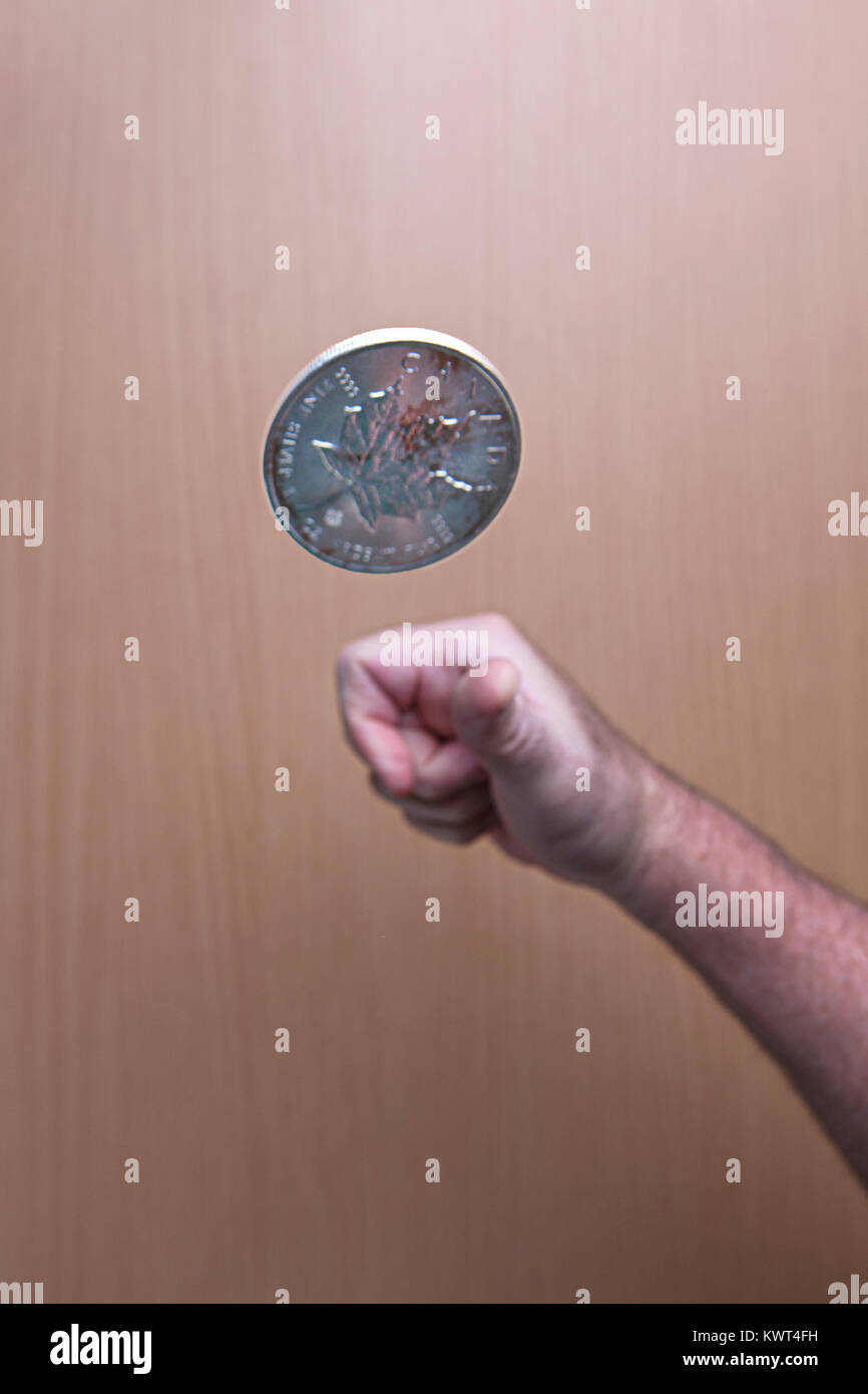 A conceptual image of flipping a Canadian silver coin up in the air. - Stock Image