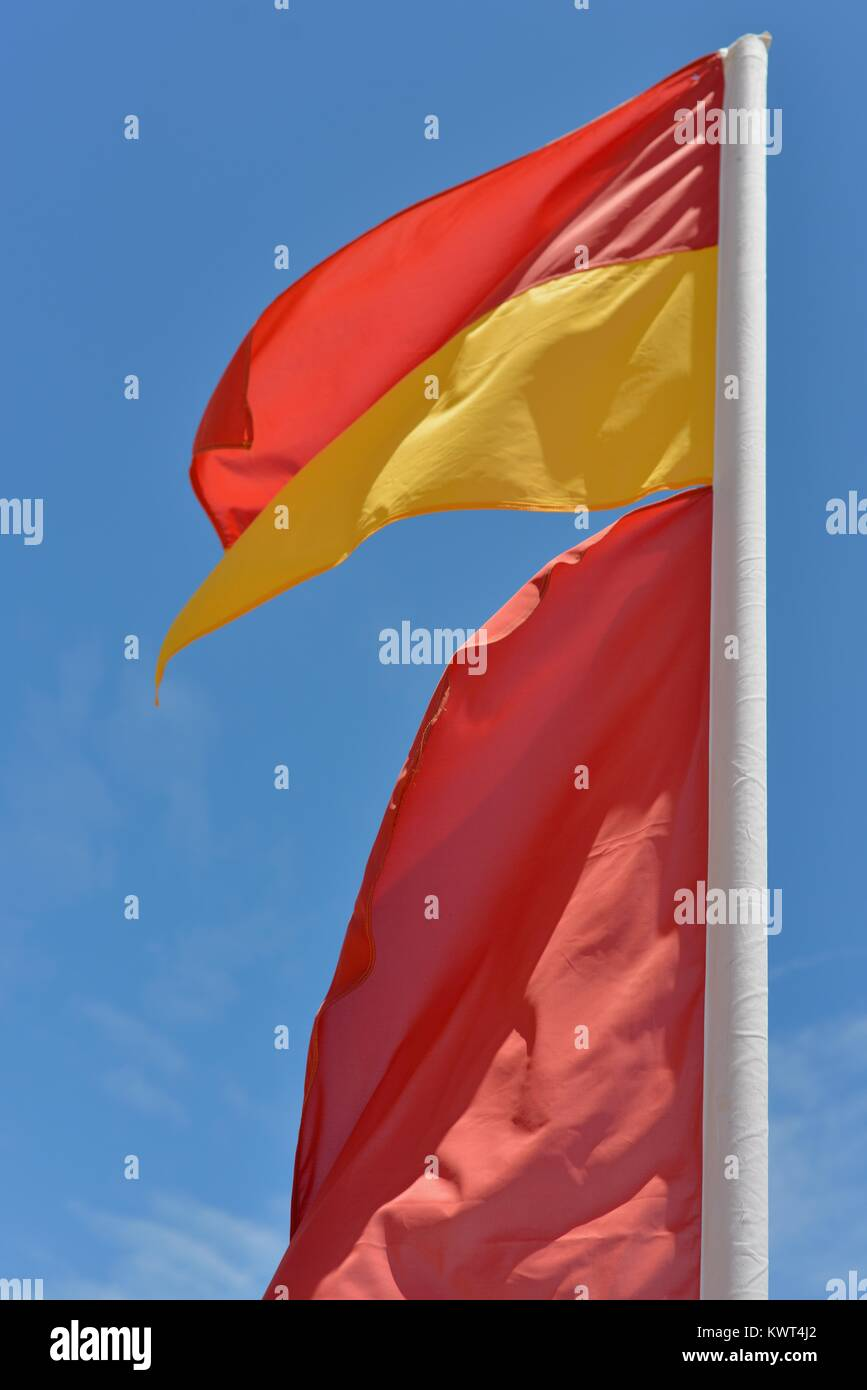 Surf lifesaving flag blowing in the wind against a blue sky background, Balgal Beach, Queensland, Australia - Stock Image