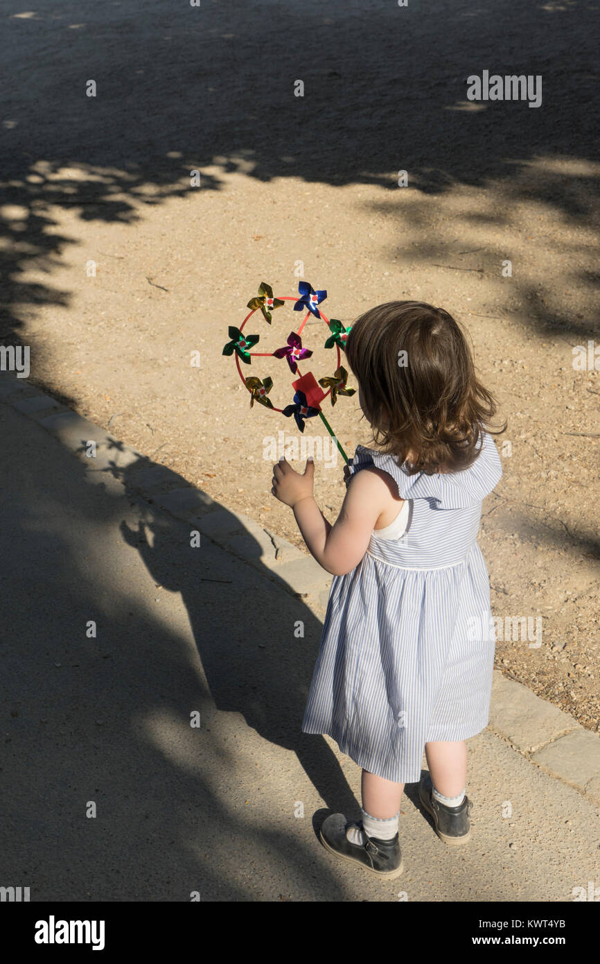 France, Paris, Little girl playing with a whirligig. - Stock Image