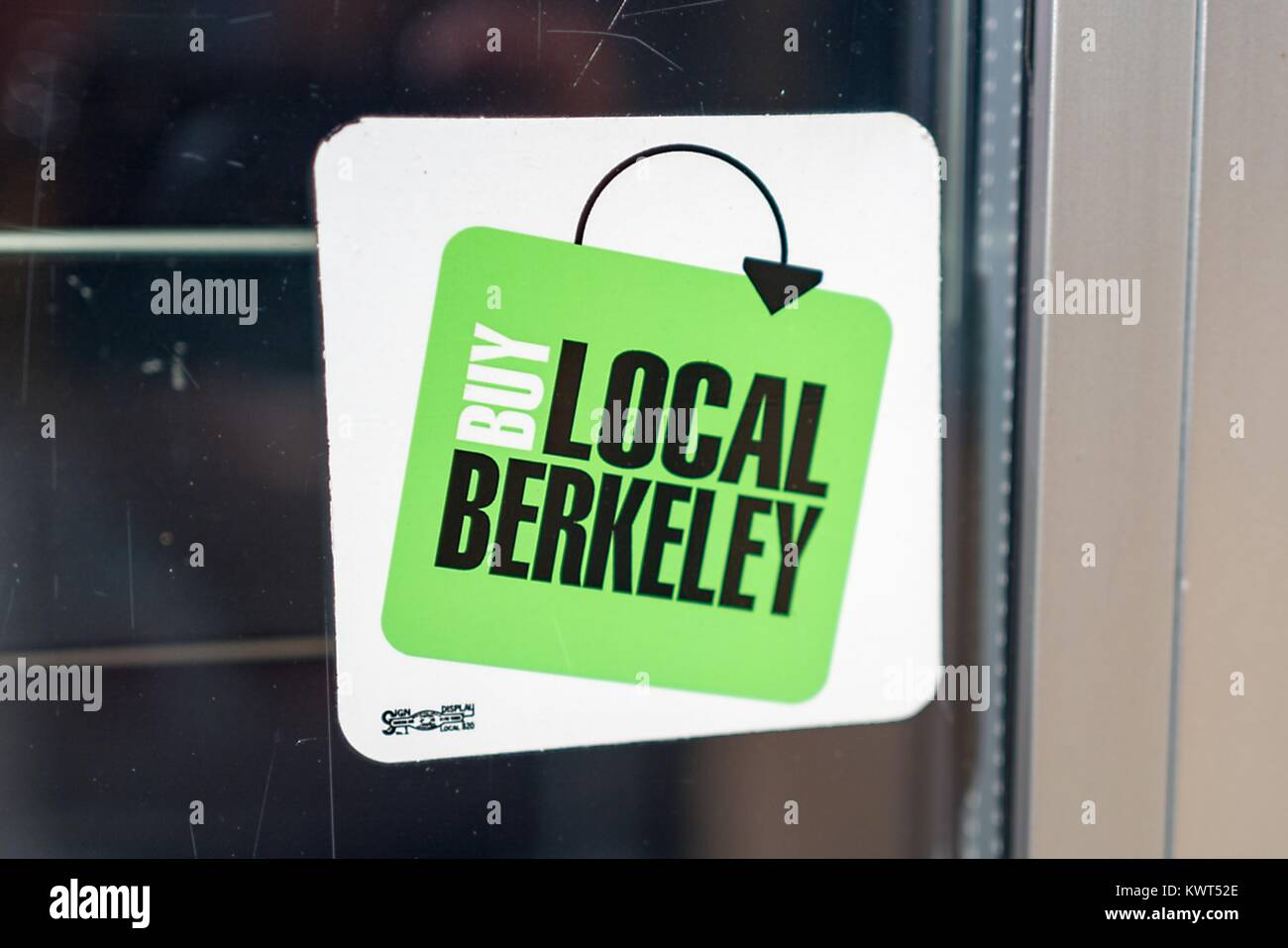 Decal on store window reading Buy Local Berkeley, encouraging visitors to make purchases from local small business - Stock Image