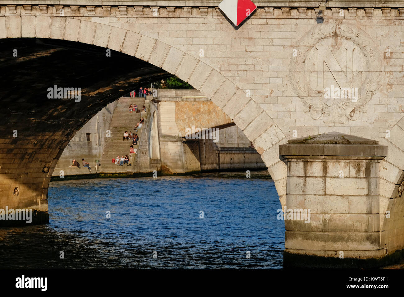 View under the Petit Pont to the Pont au Double and people sitting on the stairs going down to the Seine, Paris, - Stock Image