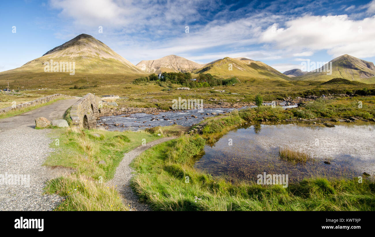 Old stone arch bridge over a mountain river at Sligachan on the Isle of Skye in the Highlands of Scotland, with Stock Photo