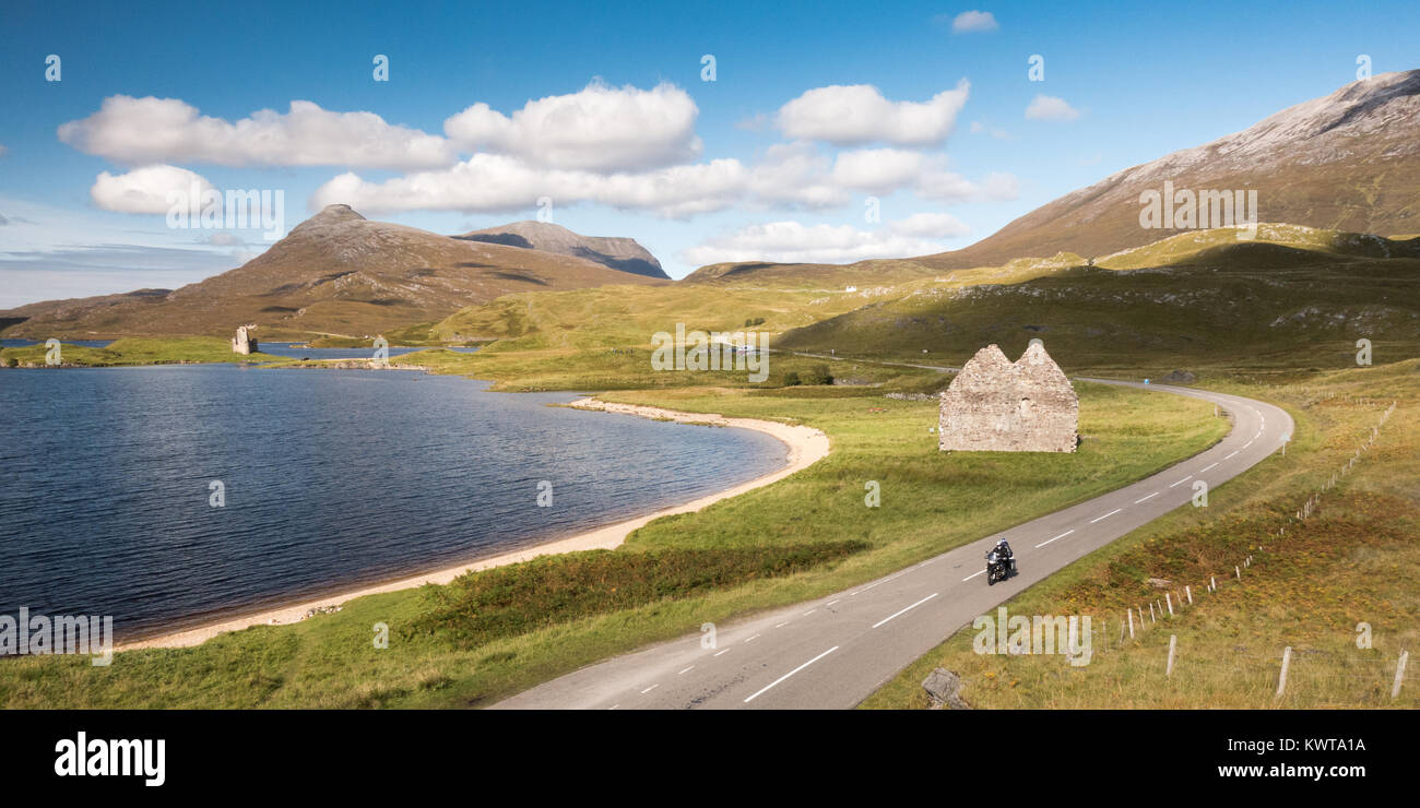 A motorcyclist passes the ruins of Calda House and Ardvreck Castle on the shores of Loch Assynt, with Quinag mountain - Stock Image