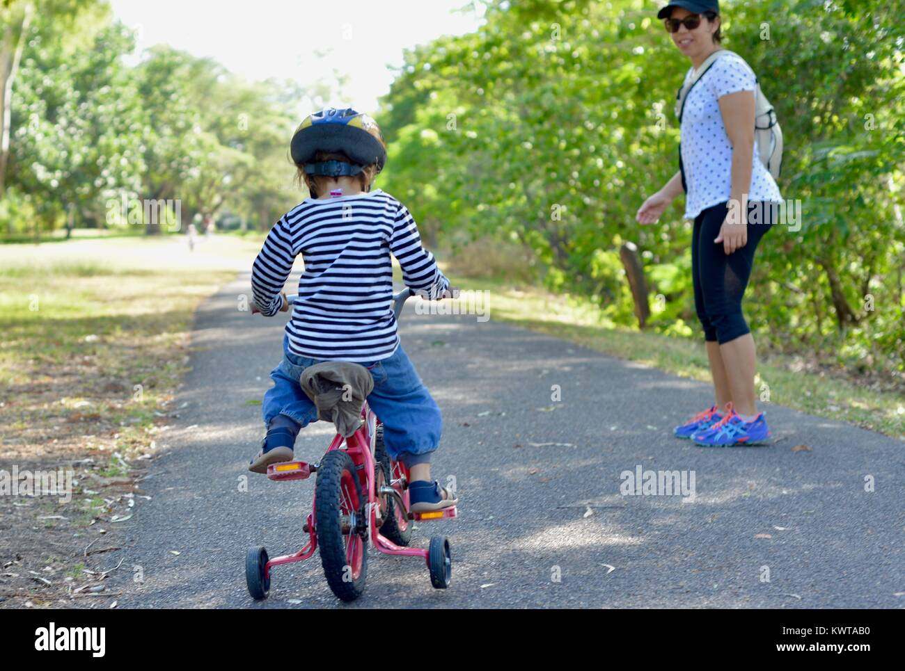 Mother walks with small child riding a bicycle with training wheels along a path, Townsville, Queensland, Australia - Stock Image
