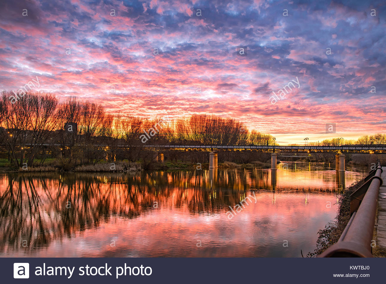 Magical sunset with magenta tones and beautiful reflections over river and over a iron bridge. - Stock Image