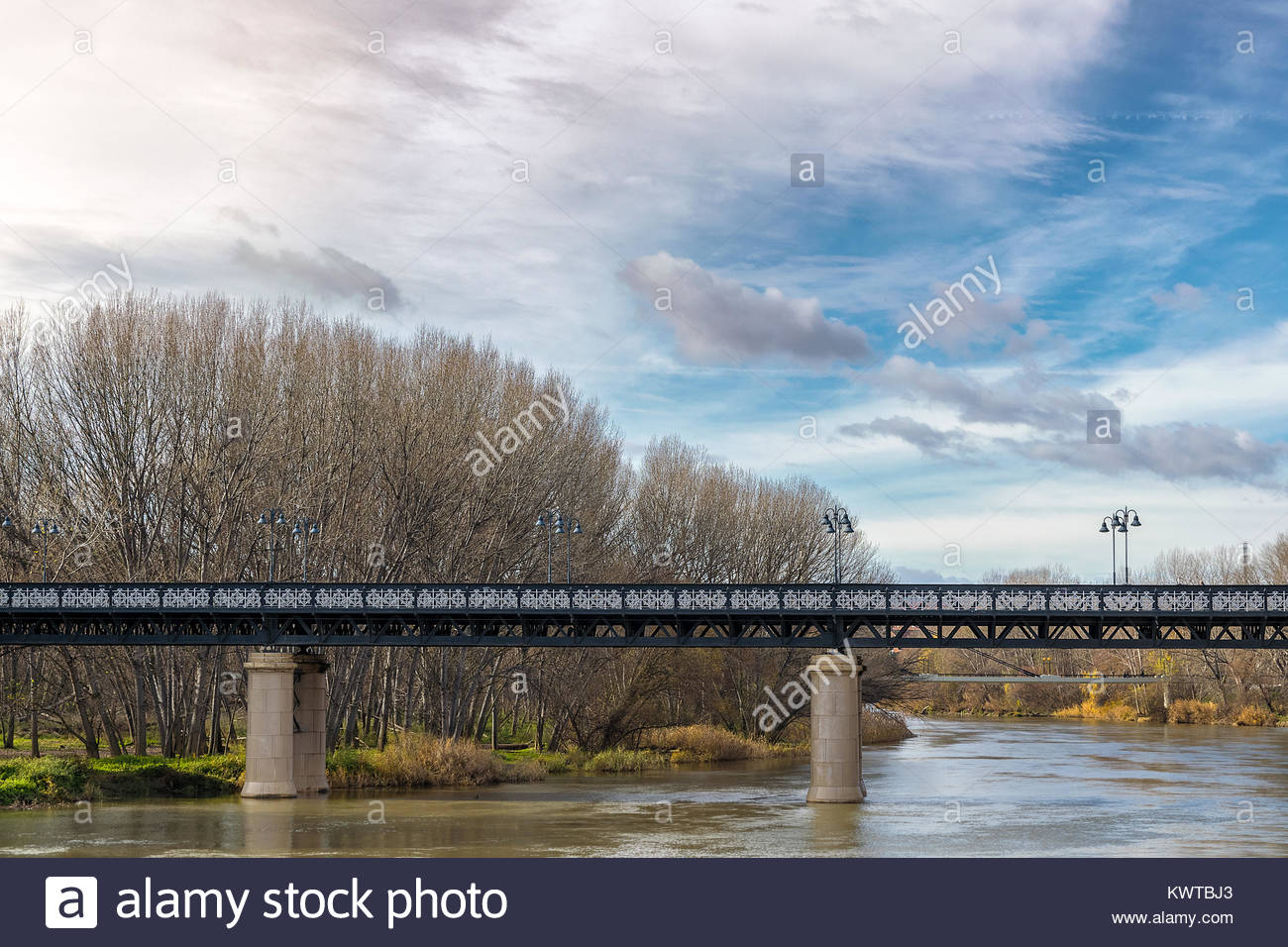 detail of iron bridge over the river and nice blue sky with white clouds and trees in winter - Stock Image