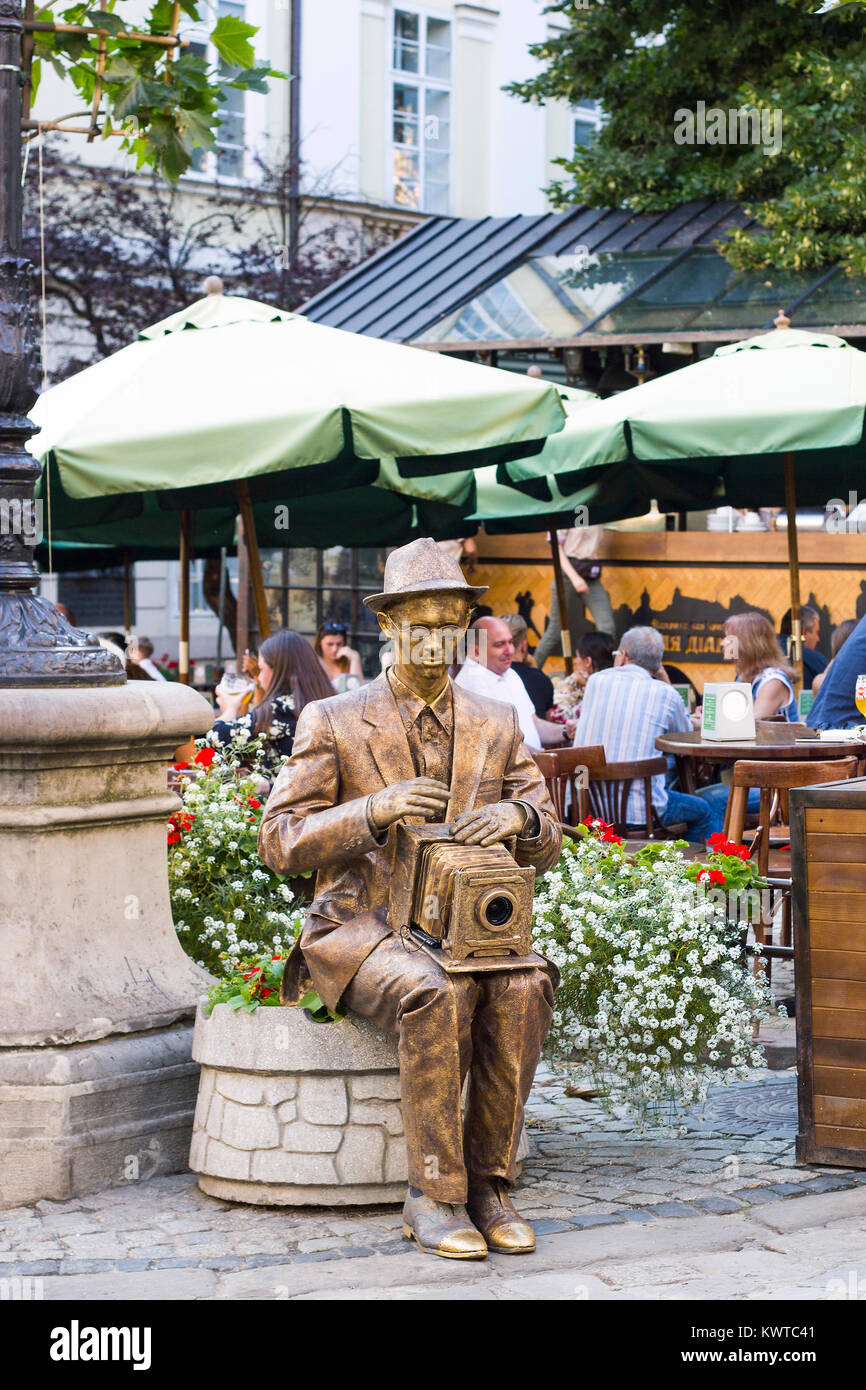 Lviv, Ukraine - July 22, 2017: Living statue gold photographer with camera sits on flower bed with flowers, summer - Stock Image