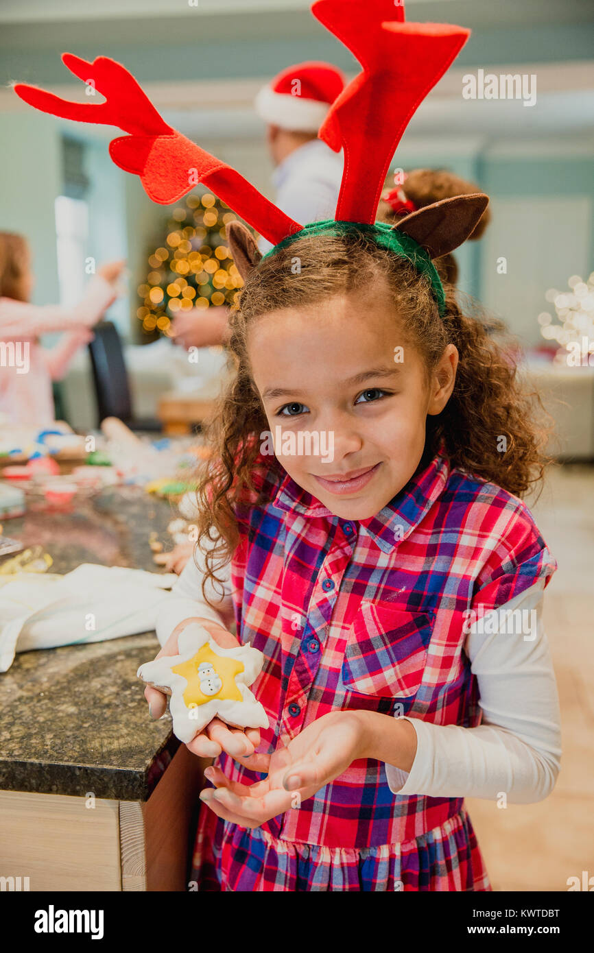 Proud little girl is posing for the camera with a christmas biscuit which she has made with her family at home. - Stock Image
