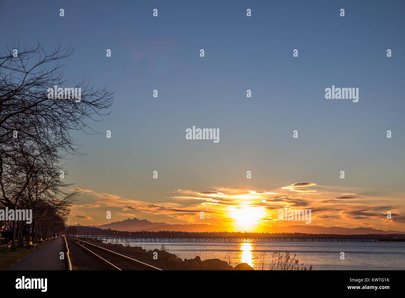 Beautiful sunrise over North Cascade Mountains, WA.. Three Fingers Mountain on horizon and railway lines along White - Stock Image