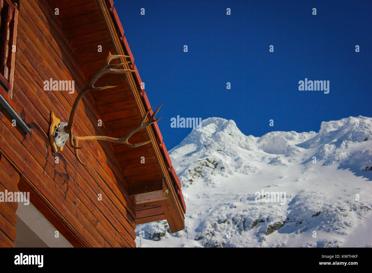 Alpine winter landscape with deer horns hunting trophy on a cabin at Balea Lake and Fagaras Mountains covered with Stock Photo
