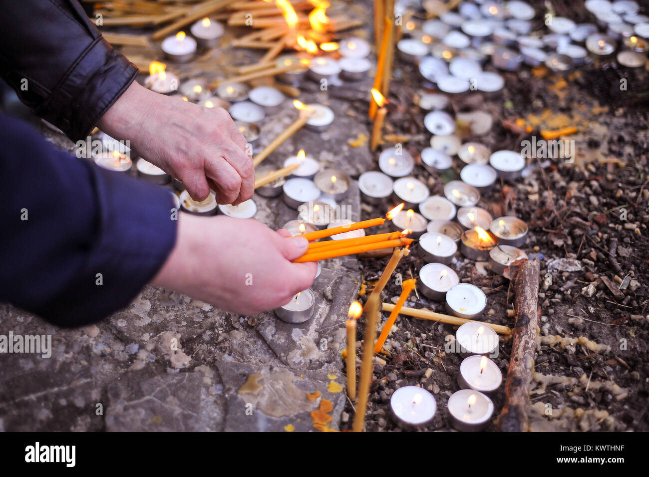 People light candles in a church yard celebrating an christian orthodox saint - Stock Image