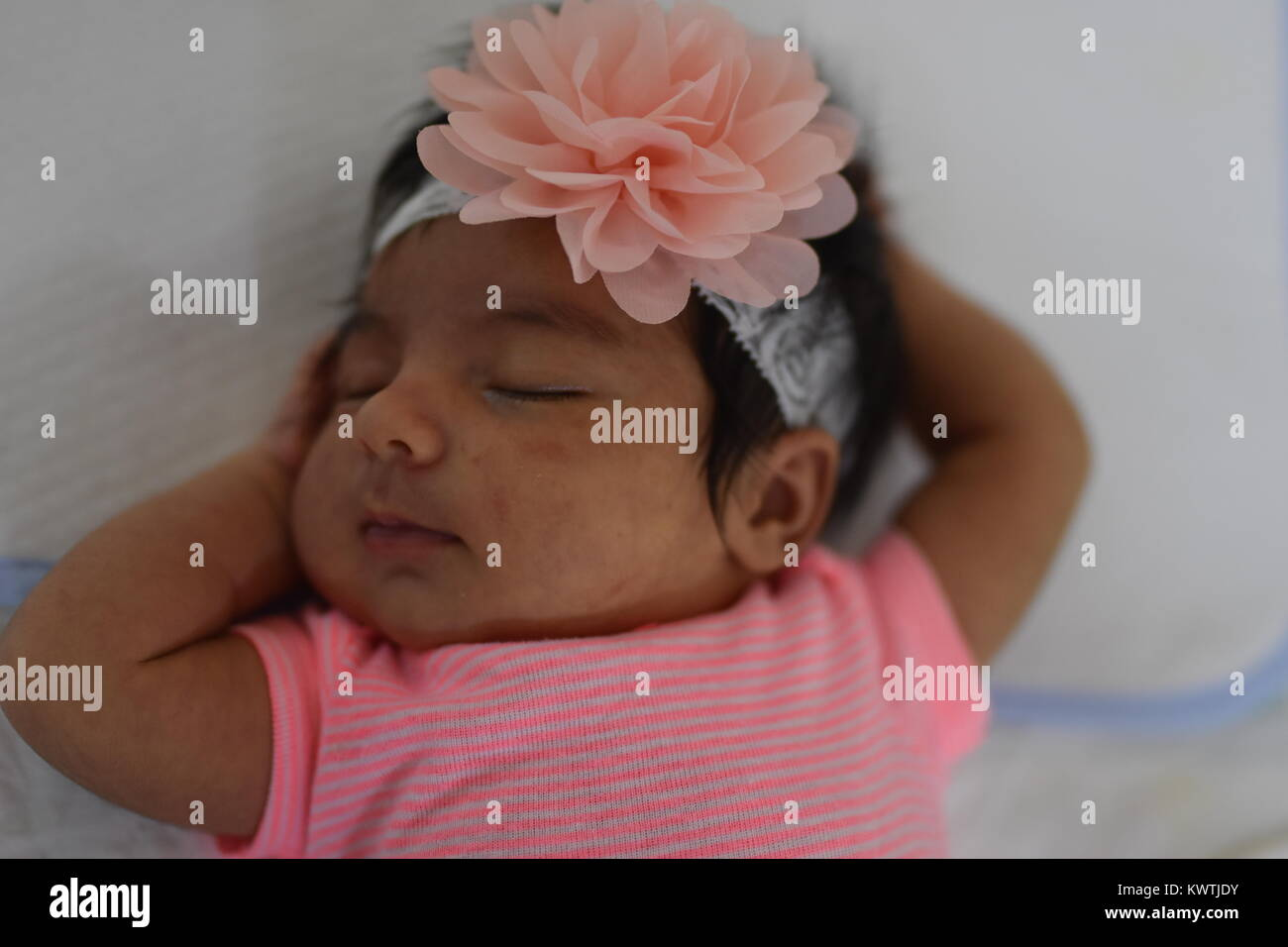 Newborn baby girl in pink sleeps peacefully on her back with arms around her head - Stock Image