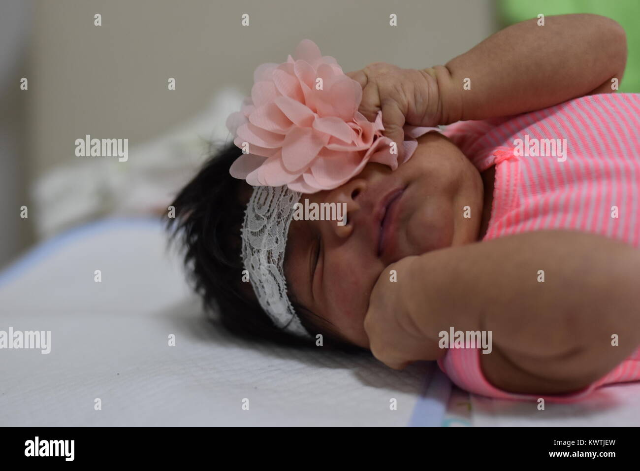 Dark skinned newborn baby girl in pink clothes laying down with eyes closed - Stock Image