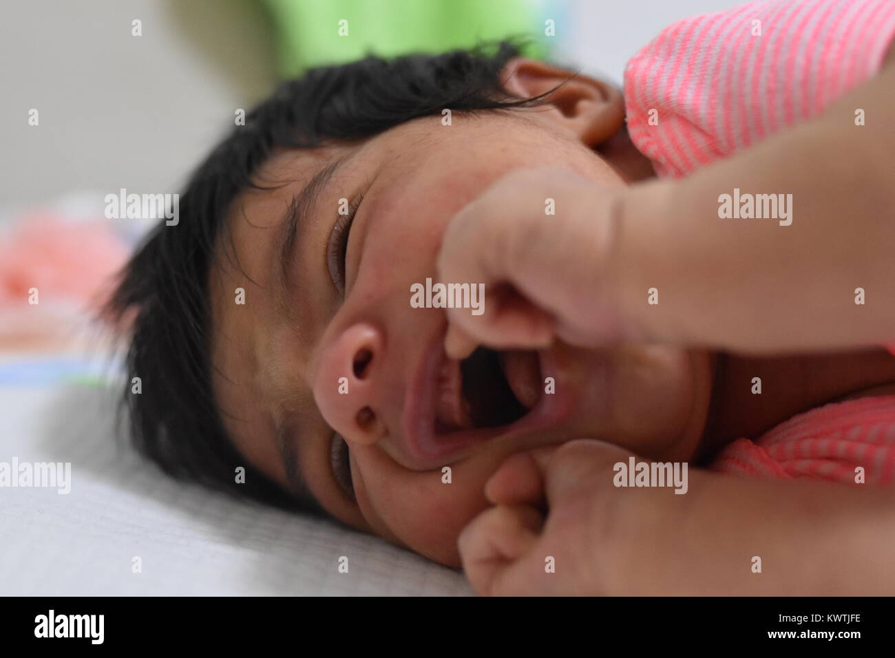 Newborn teething showing discomfort with open mouth - Stock Image