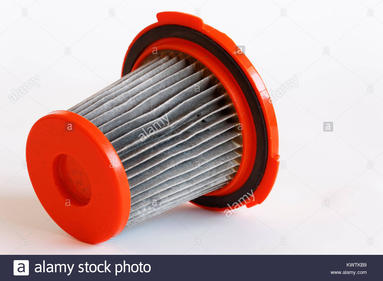 Close-up of clogged vacuum cleaner filter on white background - Stock Image