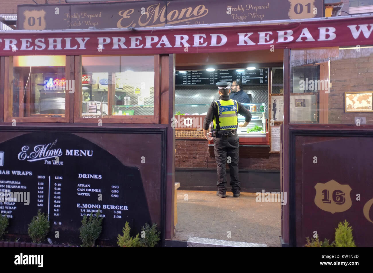 A policeman buying food from a kebab shop in London, UK. - Stock Image