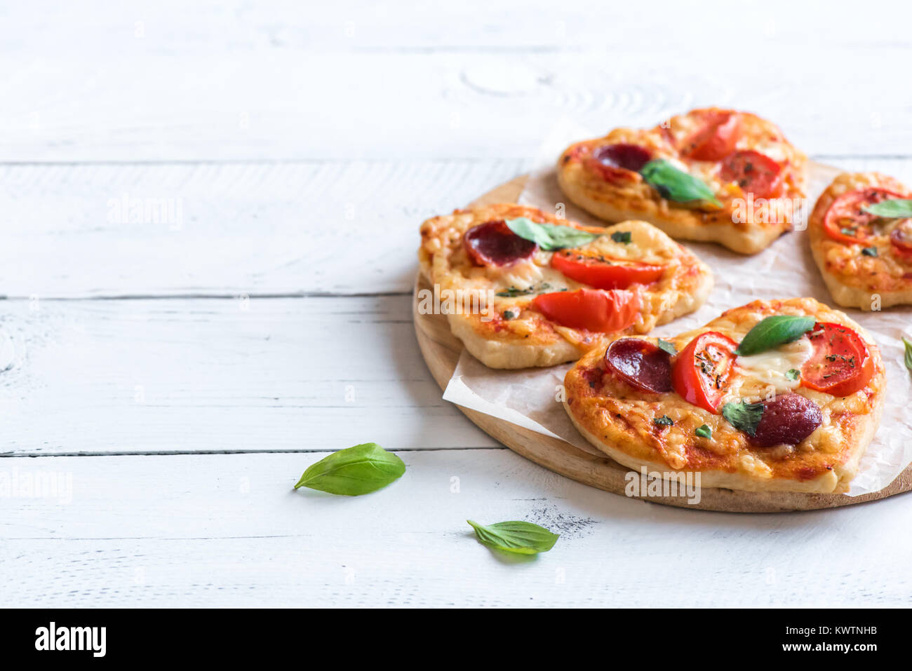 Heart shaped mini pizzas over wooden background with copy space. Mini pizzas with tomatoes, pepperoni, mozzarella - Stock Image