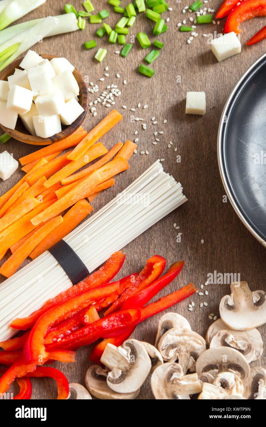 Vegetarian vegan asian food ingredients for stir fry with tofu, noodles, mushrooms and vegetables over wooden background - Stock Image