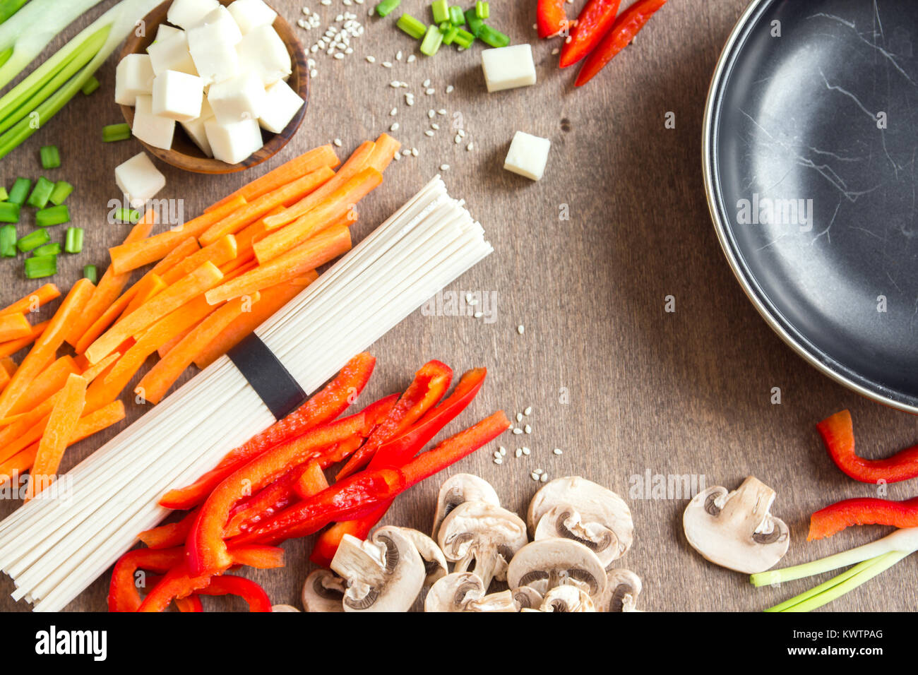 Vegetarian vegan asian food ingredients for stir fry with tofu, noodles, mushrooms and vegetables over wooden background Stock Photo