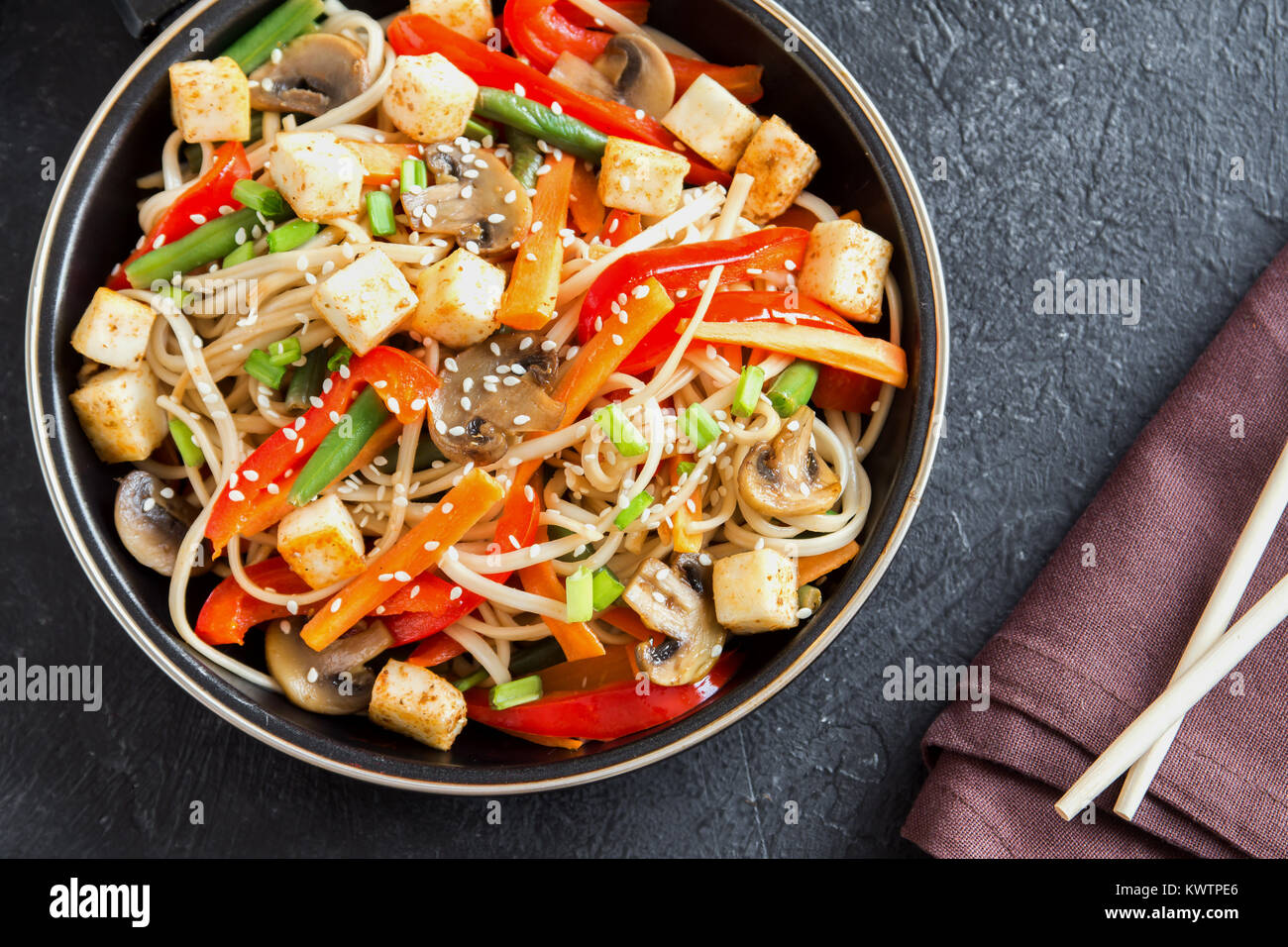 Stir fry with udon noodles, tofu, mushrooms and vegetables. Asian vegan vegetarian food, meal, stir fry in wok over - Stock Image