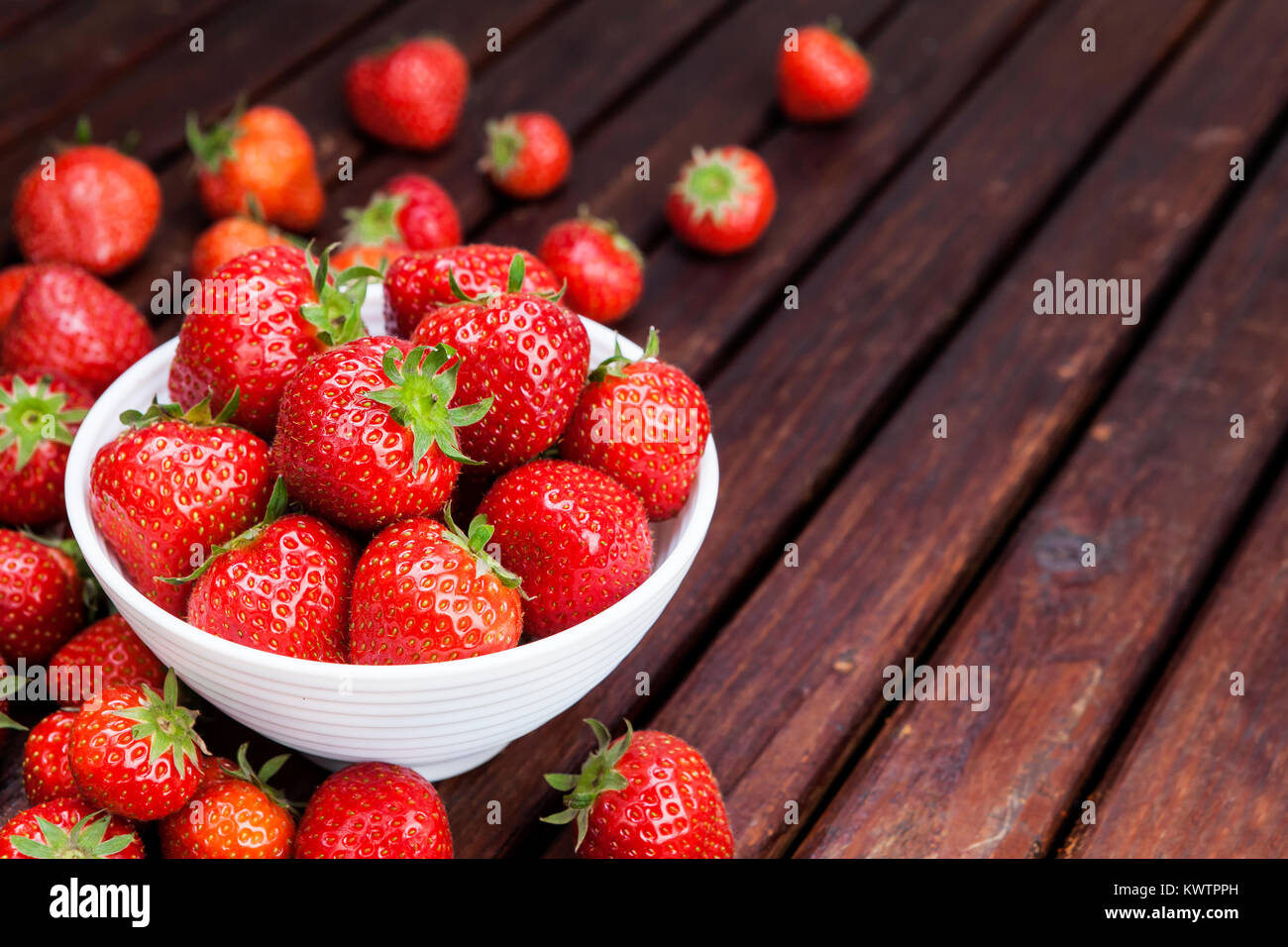 Strawberry in bowl on wooden table. Copy space - Stock Image