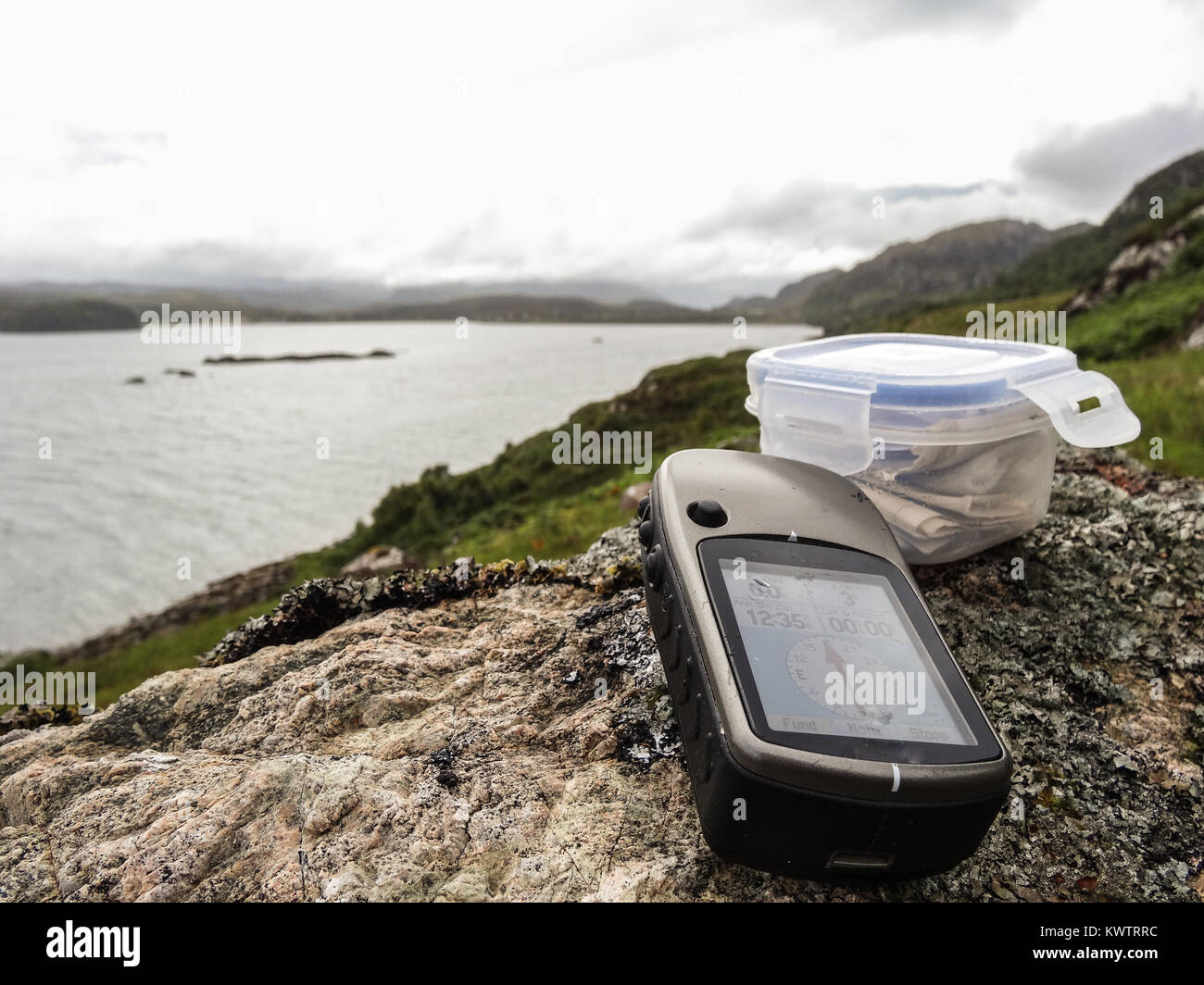 geocaching in scotland with gps device and cache container - Stock Image