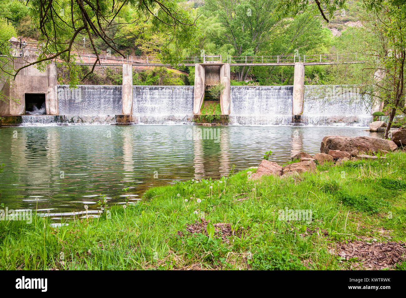 Concrete sluice with its reflection on water surface of Llobregat river in Catalonia, Spain - Stock Image