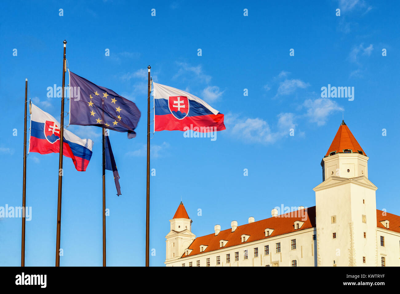 Bratislava castle and flags of Slovak republic and European Union with blue sky in background. Sunny windy day. - Stock Image