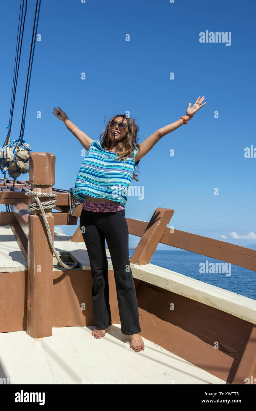 Joy of sailing, woman on old pinisi-style wooden boat, off Labuan Bajo, West Flores Island, Indonesia - Stock Image