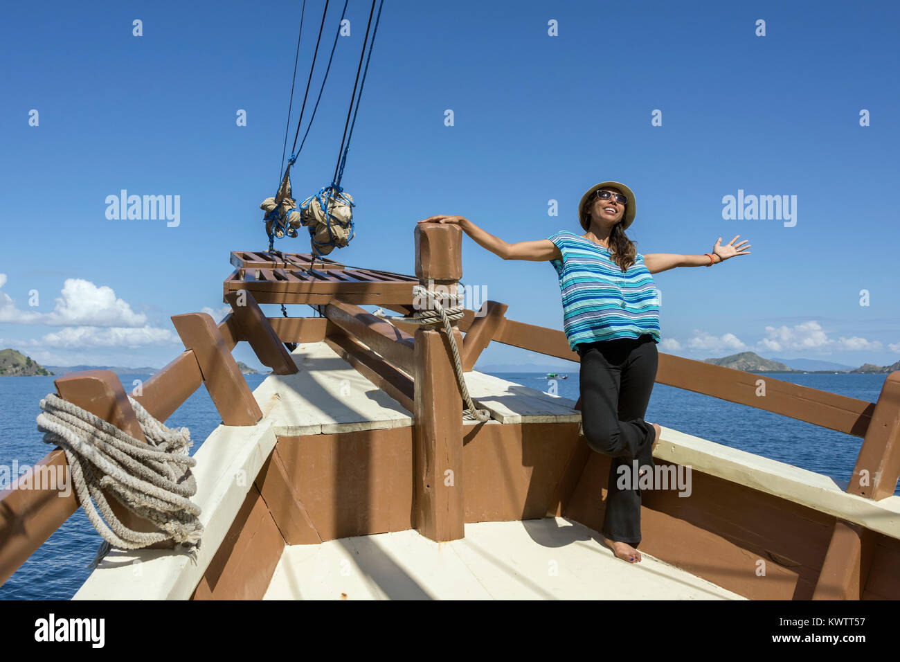 Happy woman on old pinisi-style boat off Labuan Bajo, West Flores Island, Indonesia - Stock Image
