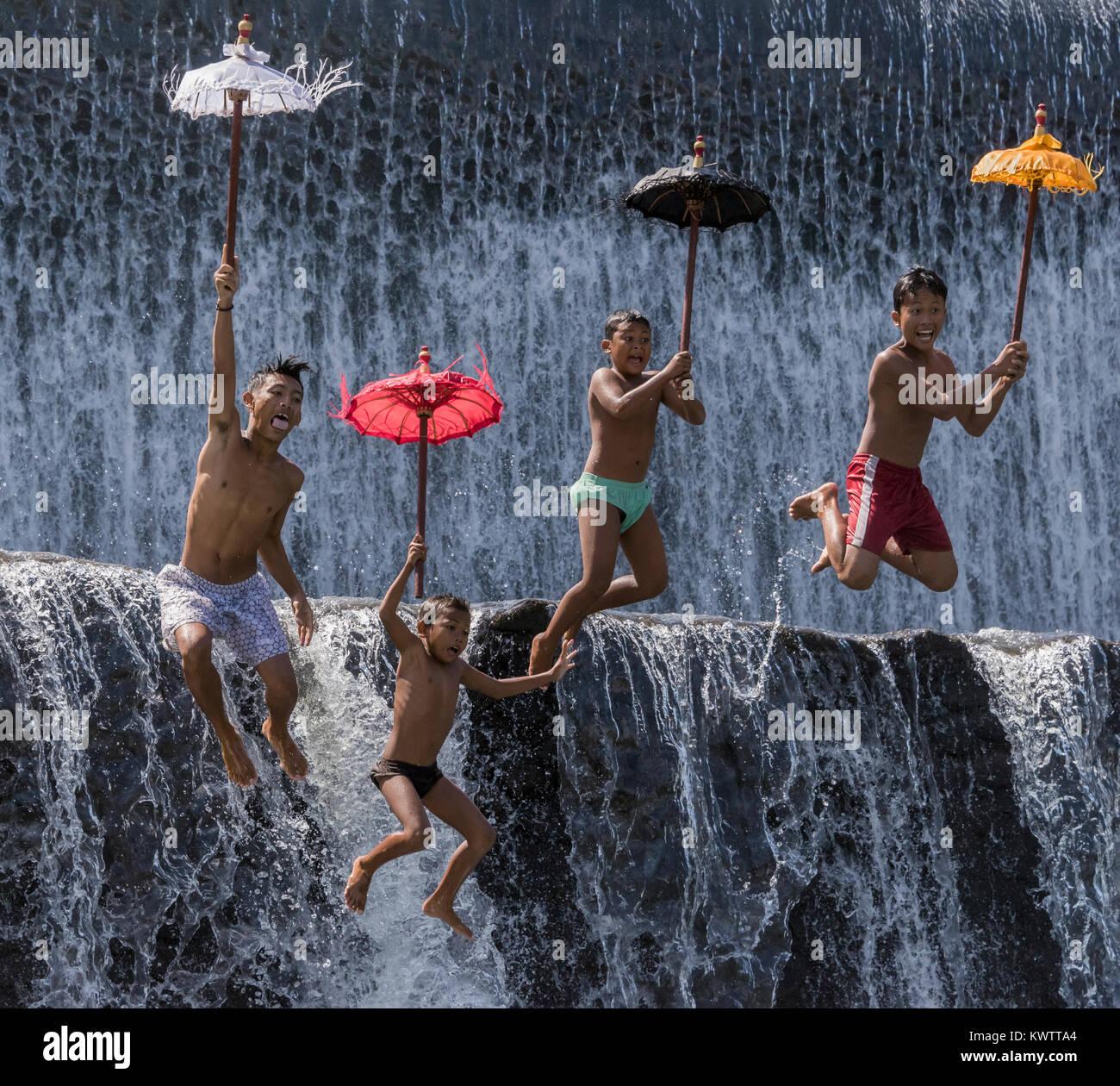 Boys leaping off a dam, Tukad Unda Dam, Semarapura, Bali Island, Indonesia - Stock Image