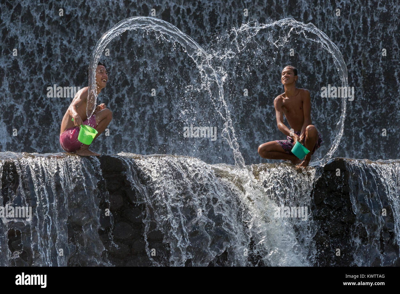 Water heart made by boys playing in the water at Tukad Unda dam on a hot day, Bali Island, Indonesia - Stock Image
