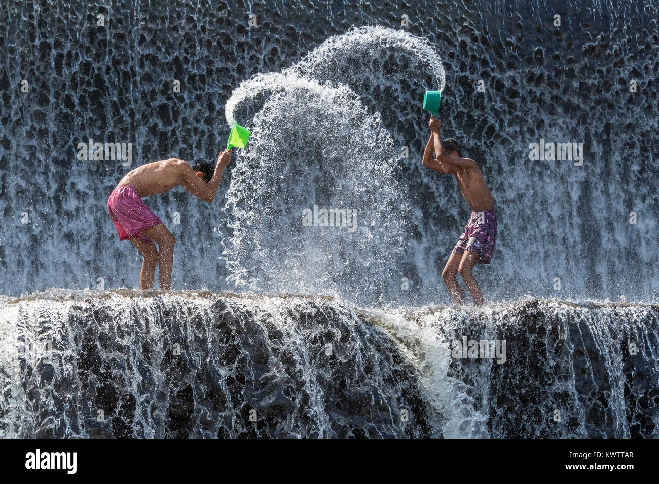 Two boys playing in the water at Tukad Unda dam on a hot day, Bali Island, Indonesia - Stock Image