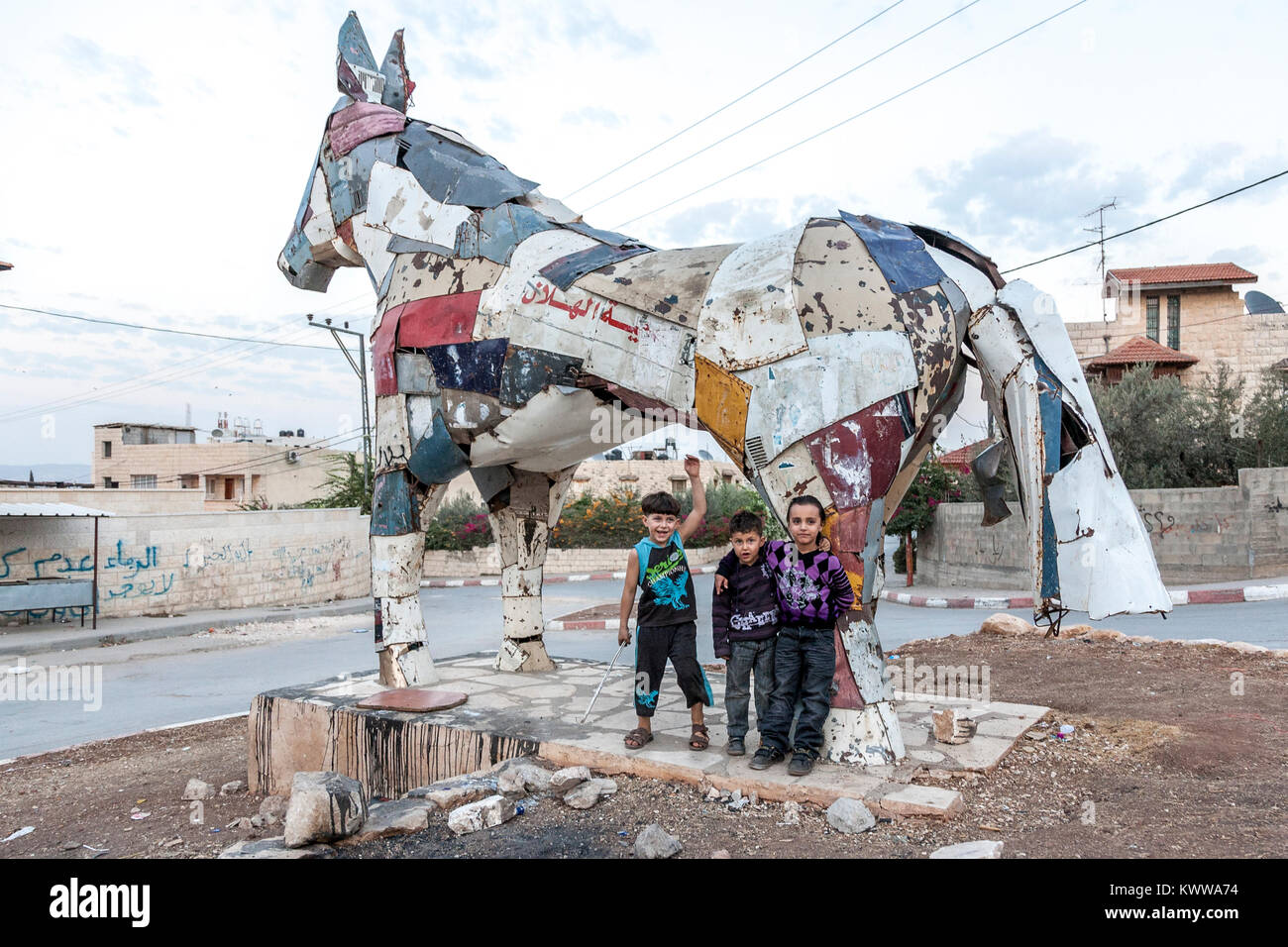 Jenin, Palestine, November 18, 2010: Palestinian children are standing in front of a horse built by German artist Stock Photo