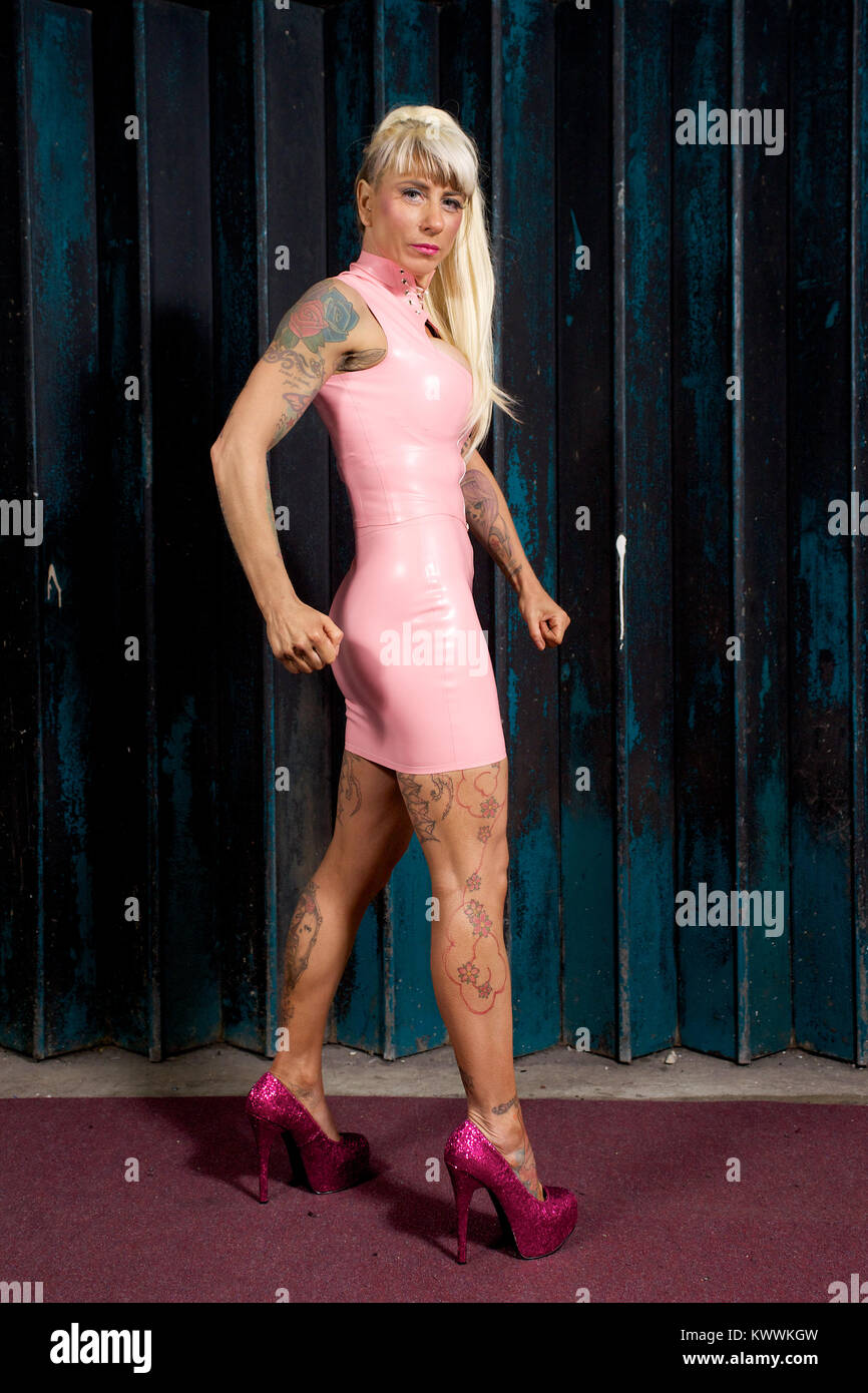 Muscular blonde girl in a pink pvc dress and high heels - Stock Image