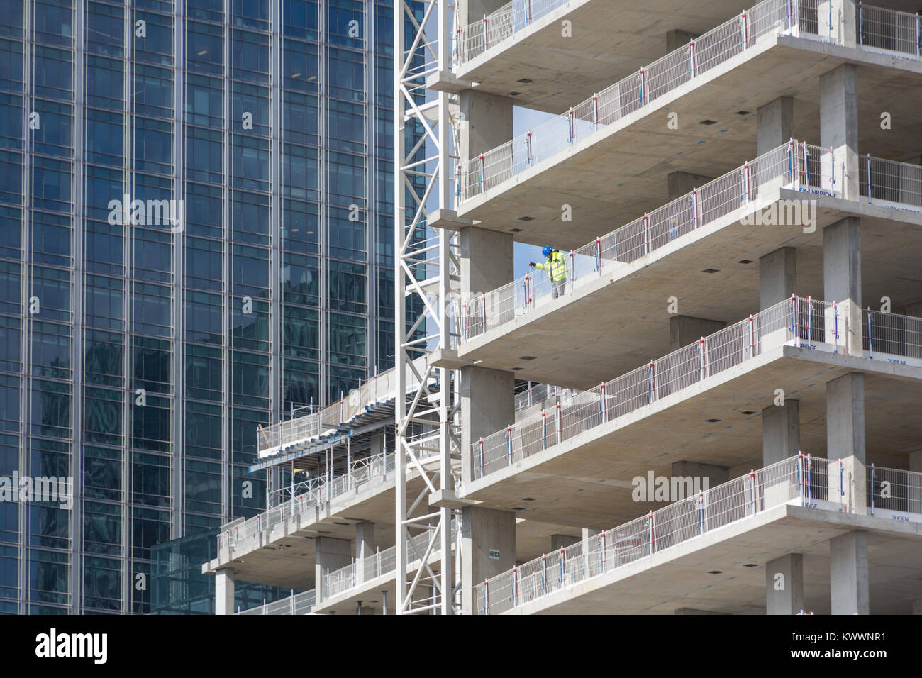 Construction workers and crane at work buildi construction site in London Docklands area at Canary Wharf - Stock Image