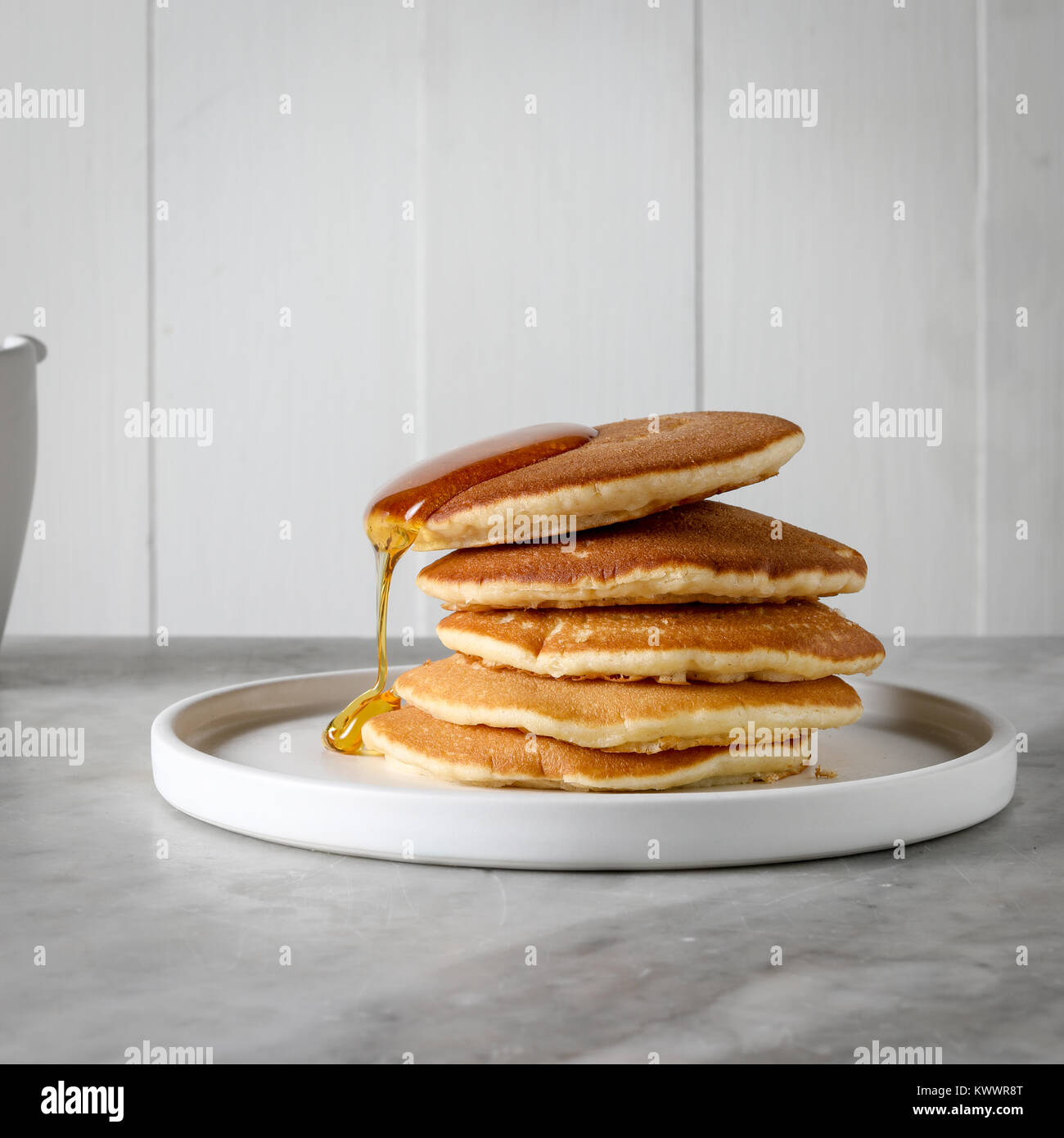 A stack of pancakes with a slow drip of honey - Stock Image