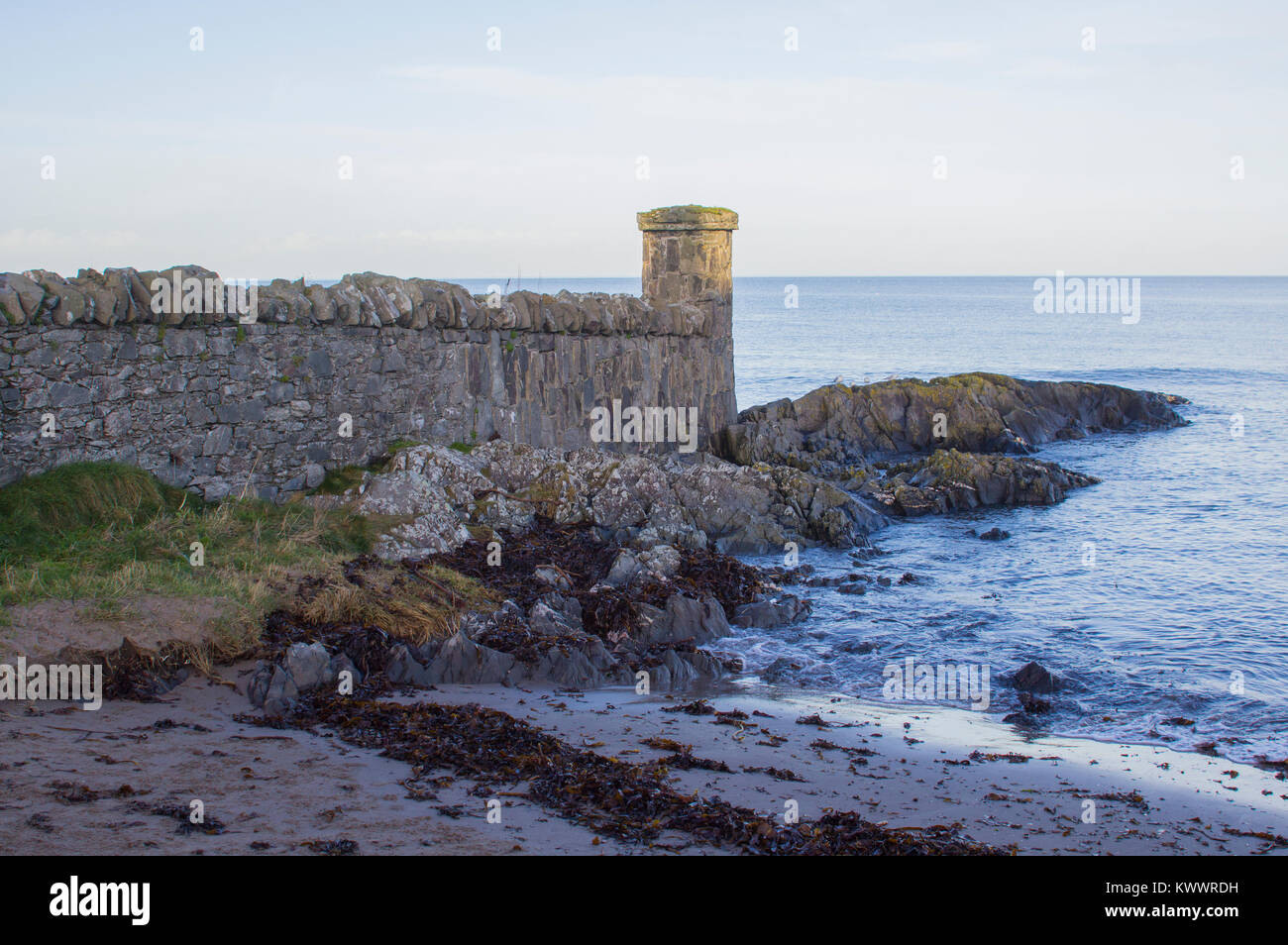 The rocky foreshore and the stone built replica fortifications at the seaside village of Groomsport in Count Down - Stock Image