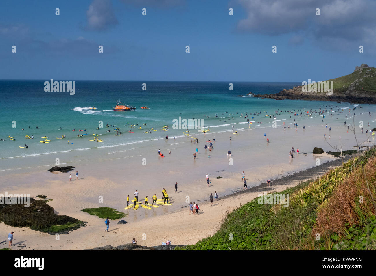A summers day at St Ives beach in Cornwall. The RNLI lifeboat patrols offshore while surfers and tourists enjoys - Stock Image