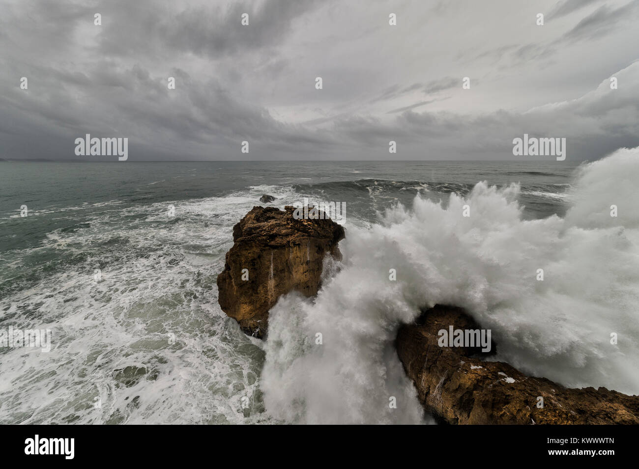 crashing waves with a moody sky at Farol da nazare - Stock Image