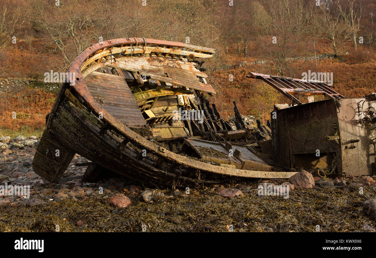 An old decaying fishing boat from yesteryear lies on the shoreline at Diabaig, Torridon in the Scottish Highlands Stock Photo