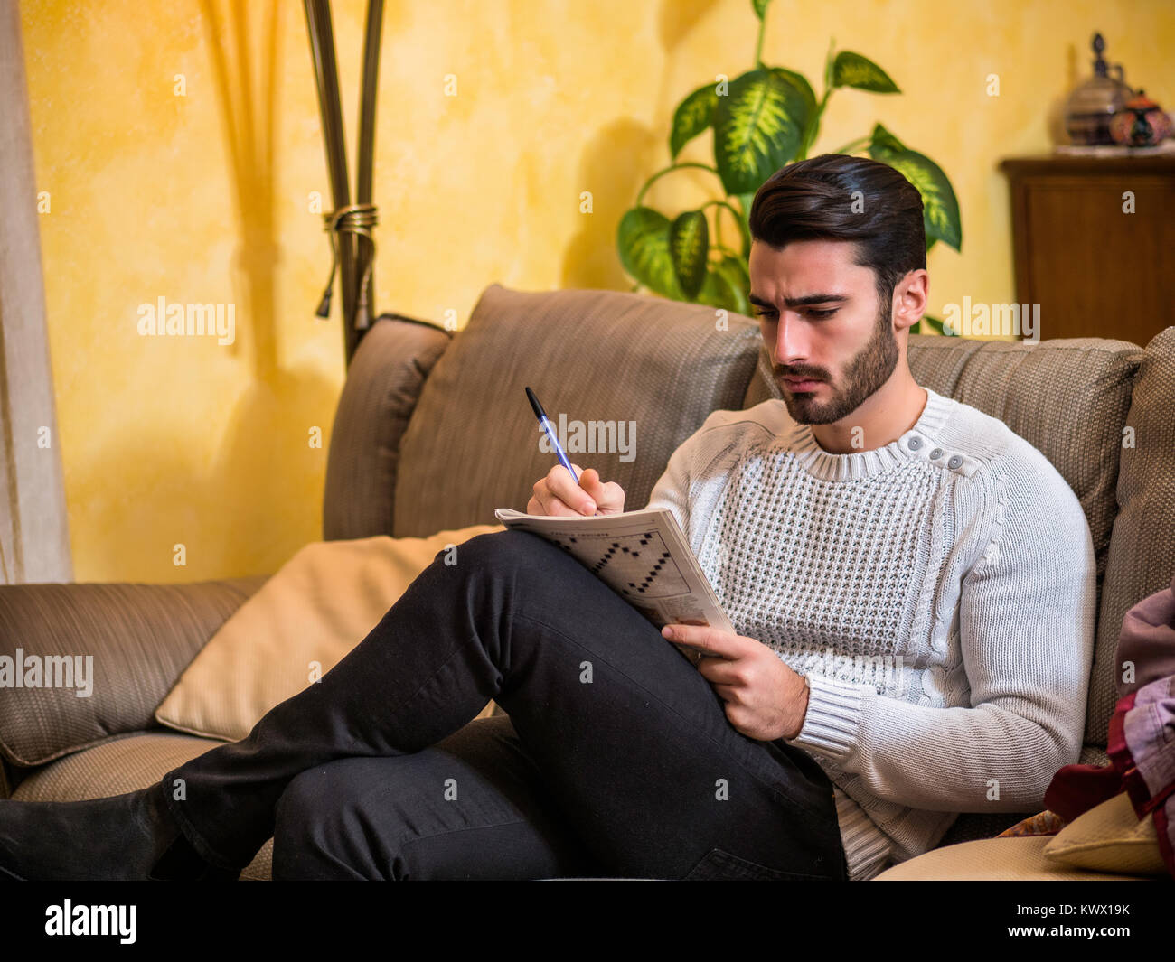 Young Man Sitting Doing A Crossword Puzzle Looking Thoughtfully At A Stock Photo Alamy