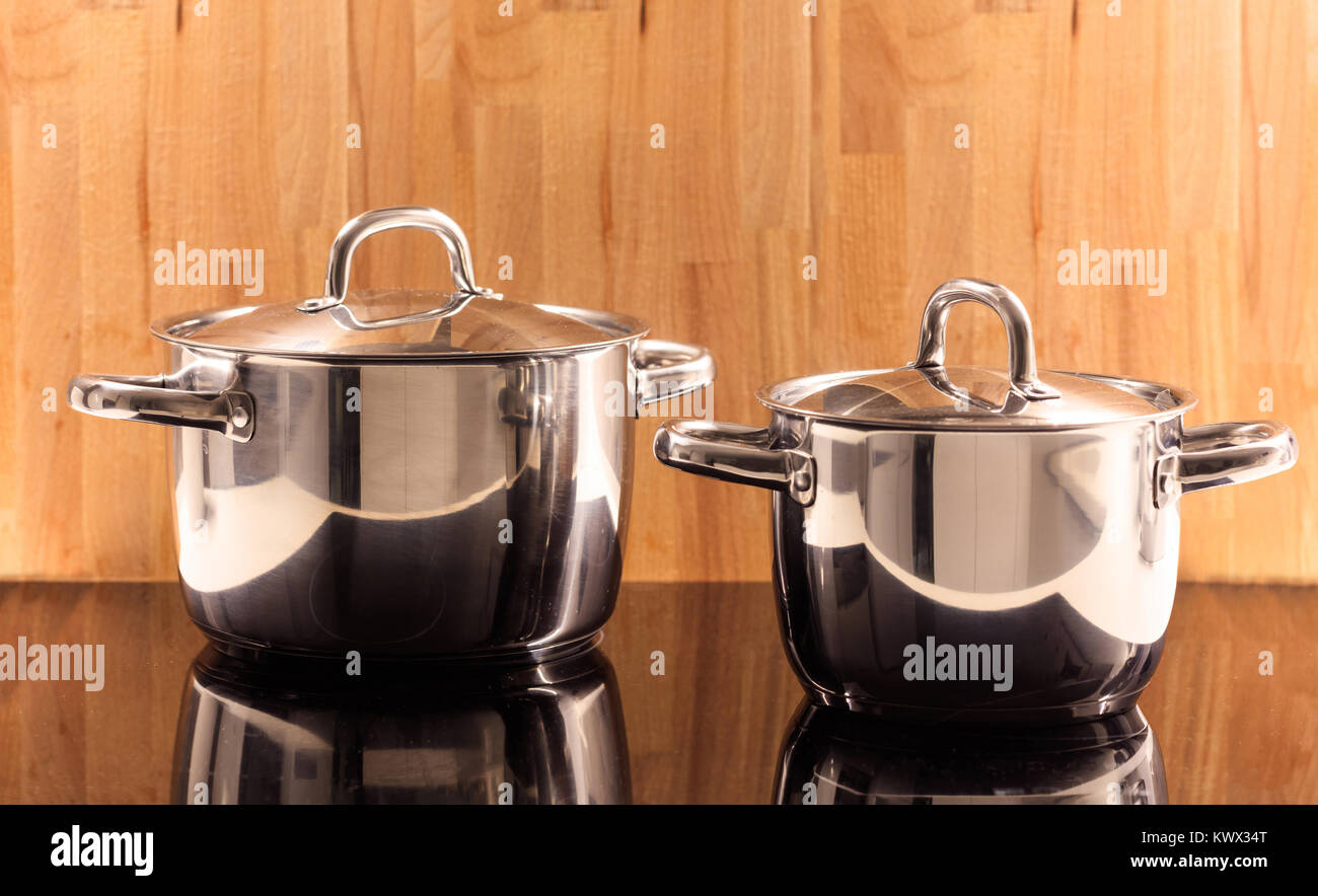 Traditional cooking pots placed on ceramic hob. Wooden background. Reflection, close up, details. - Stock Image