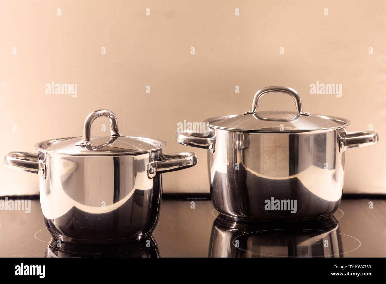 Cooking pots placed on modern electric ceramic stove. Reflections, closeup, details. - Stock Image