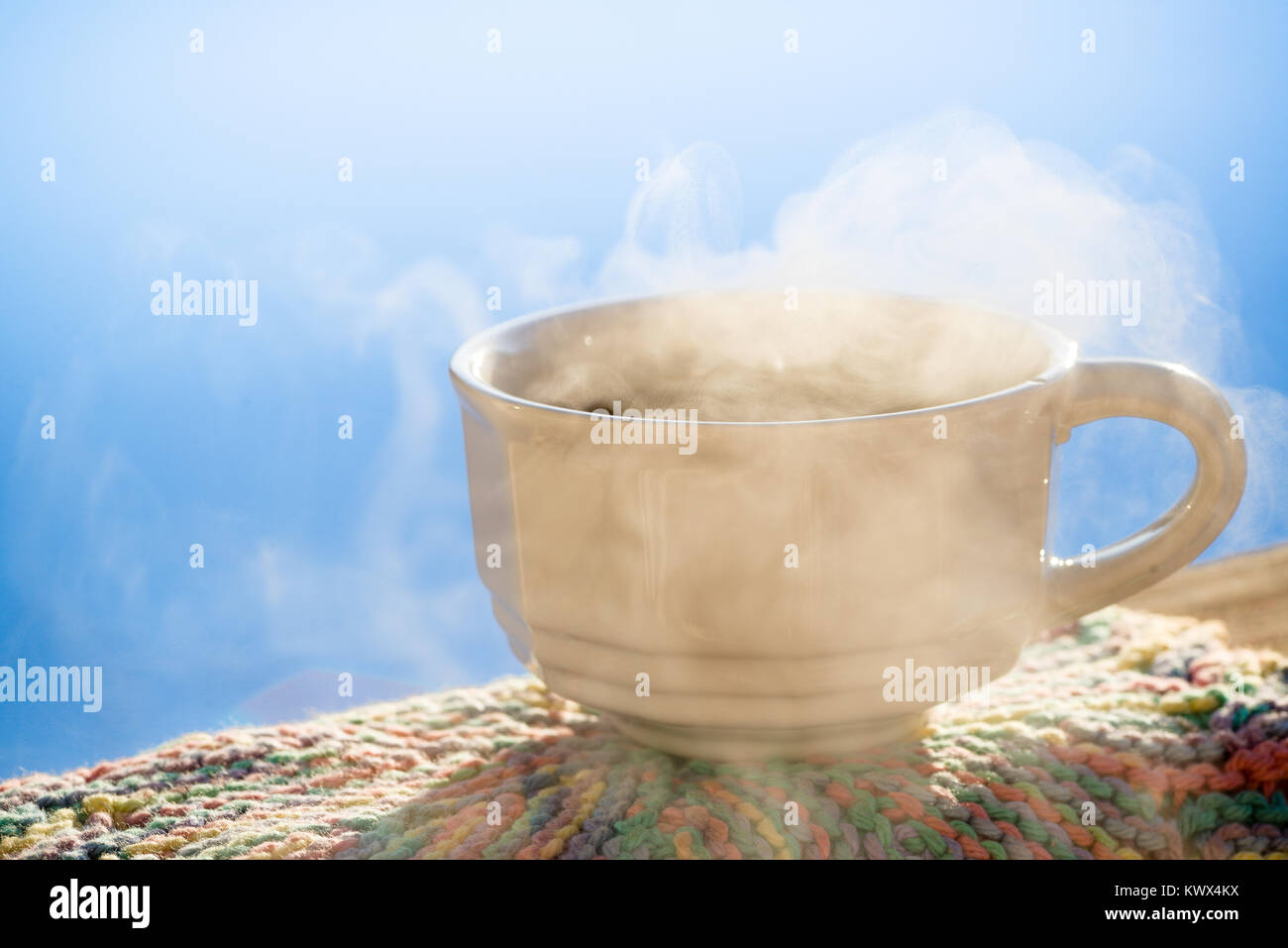 Horizontal image white antique cup of black coffee sitting on railing with steam rising. Blue sky colorful hand - Stock Image