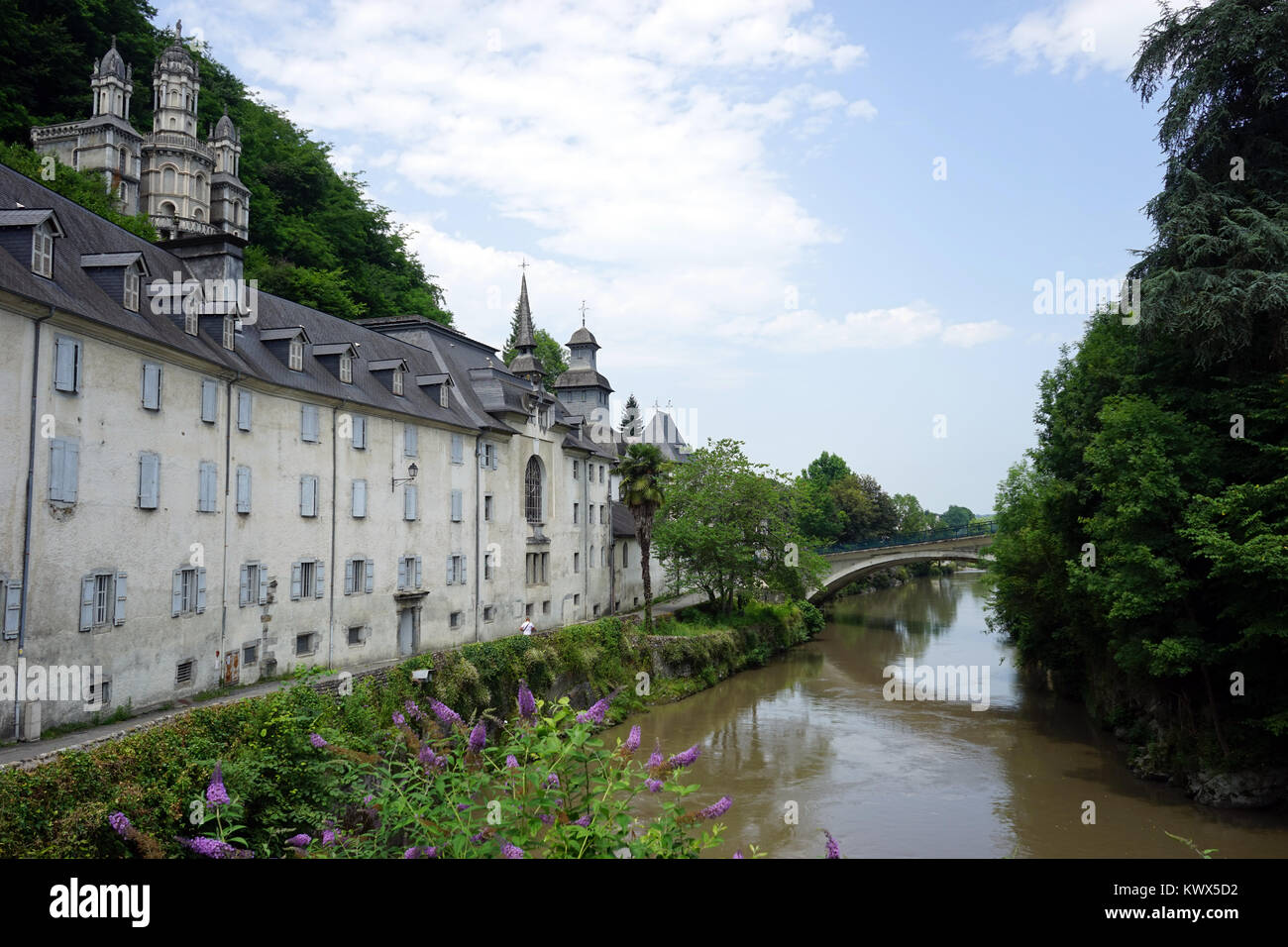 LESTELLE-BETHARRAM, FRANCE - CIRCA JULY 2015 Facade of monastery and bridge on the river Stock Photo