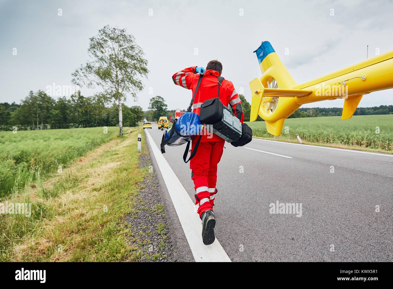 Doctor with defibrillator and other equipment running from helicopter. Teams of the Emergency medical service are - Stock Image